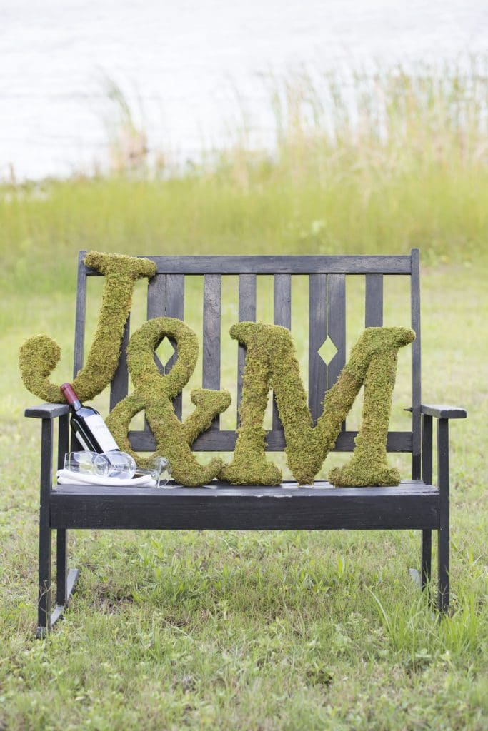 The Magnolia Company - moss-covered couple's initials on bench outdoors