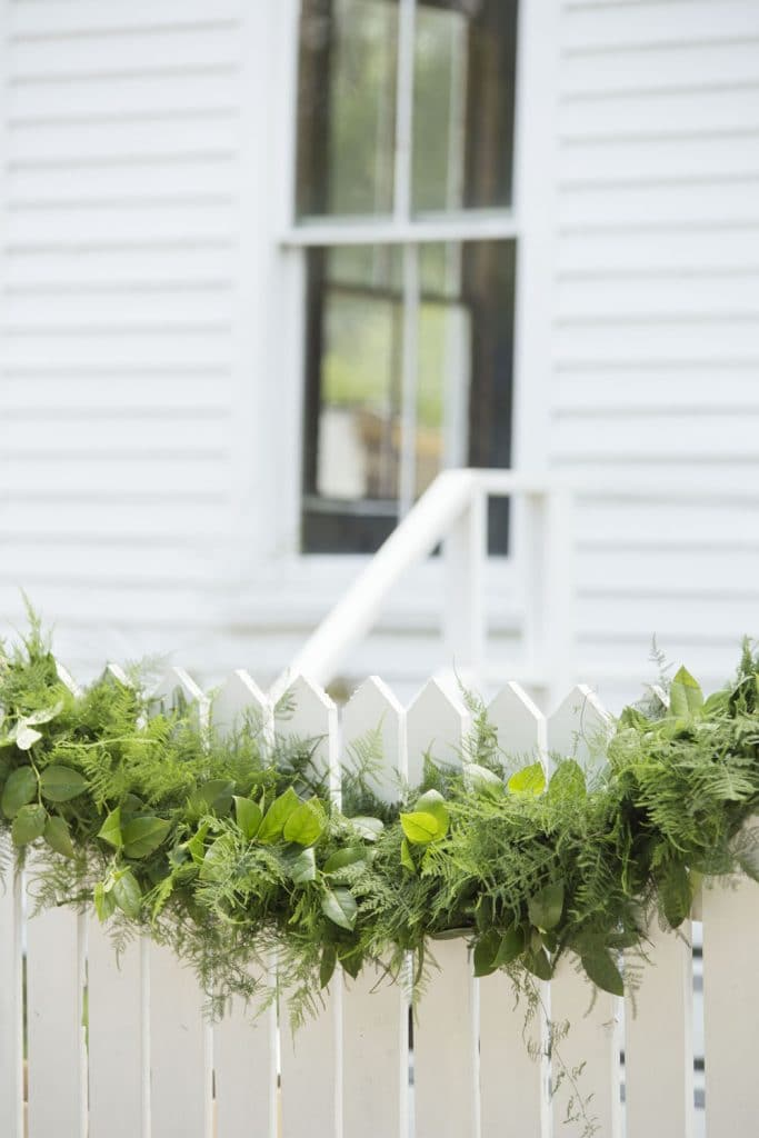 The Magnolia Company - greenery swag on white picket fence