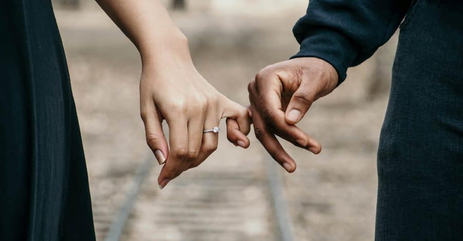 Engagement photo shoot, closeup of couples linking pinkies