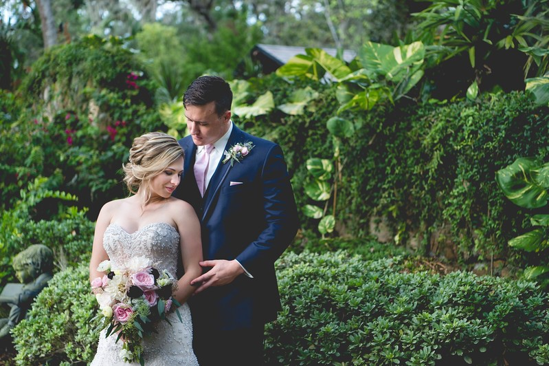 Estate on the Halifax - Bride and Groom pose in front of greenery covered wall outdoors with mixed rose bouquet