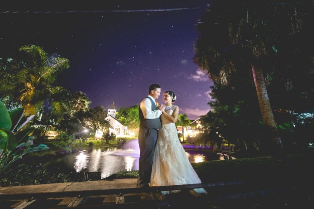 Estate on the Halifax - Bride and Groom embrace in front of fountain next to train tracks with starry night sky in background