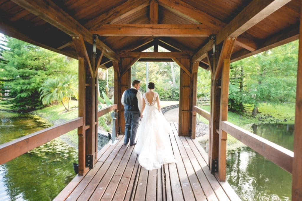Estate on the Halifax - Bride and Groom walk on wooden bridge with train tracks over water