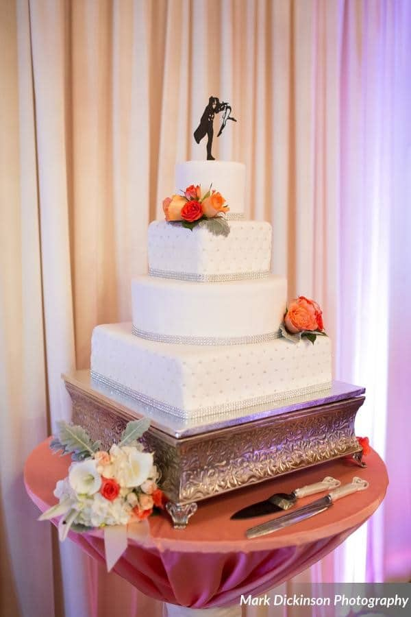 Estate on the Halifax - Four tier mixed square and round wedding cake with orange and white toned flowers on covered stand with cake topper