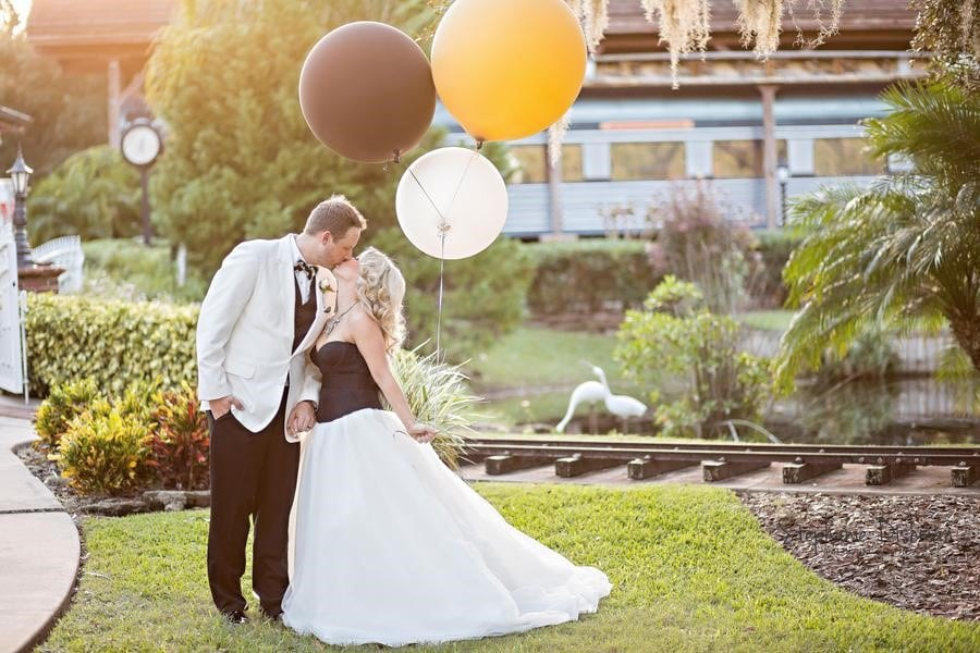Estate on the Halifax - Bride and Groom kissing outdoors next to train tracks while hold large colored balloons