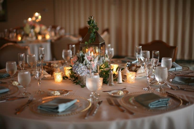 Sugar-Mill-Country-Club-Low light table setting with candles and crystal glasses on table with small centerpiece