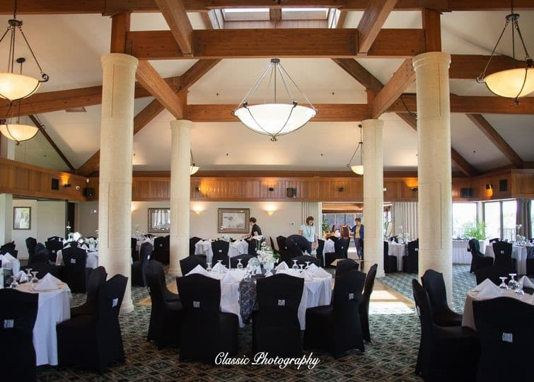 Sugar-Mill-Country-Club-Indoor reception hall with black chair covers and white table covers