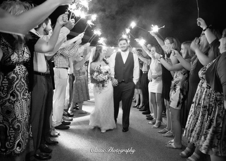 Sugar-Mill-Country-Club-Black and white image of bride and groom walking out during send off with guests holding sparklers