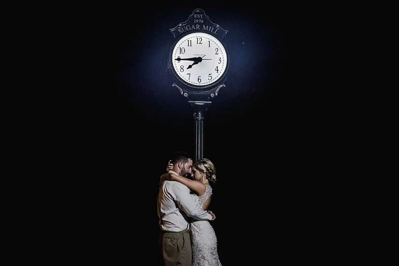 Sugar-Mill-Country-Club-Couple standing in front of clock at night in moonlight