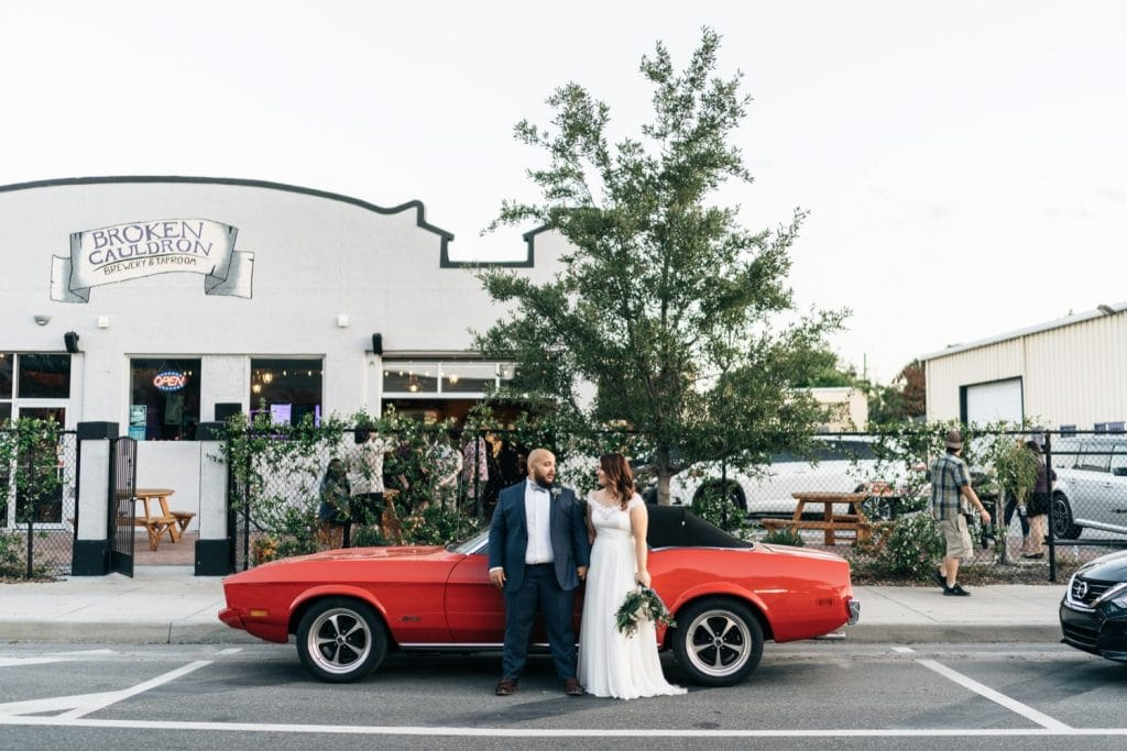 1010-West-Bride and Groom standing in front of older model car outdoors