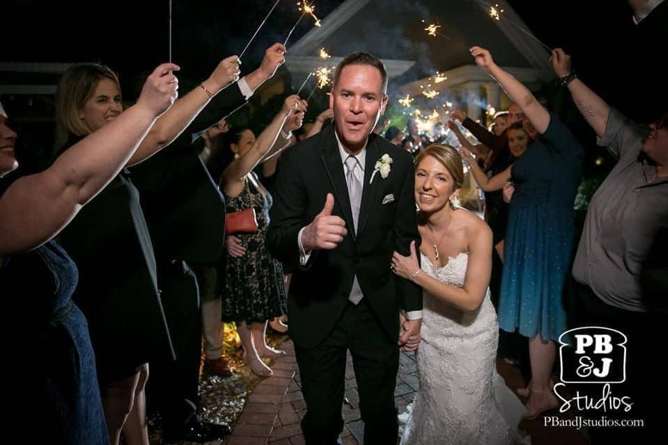 bride and groom giving thumbs up as they walk through wedding guests holding sparklers