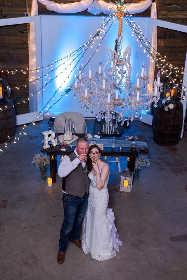 bride and groom standing under large chandelier at wedding receptions