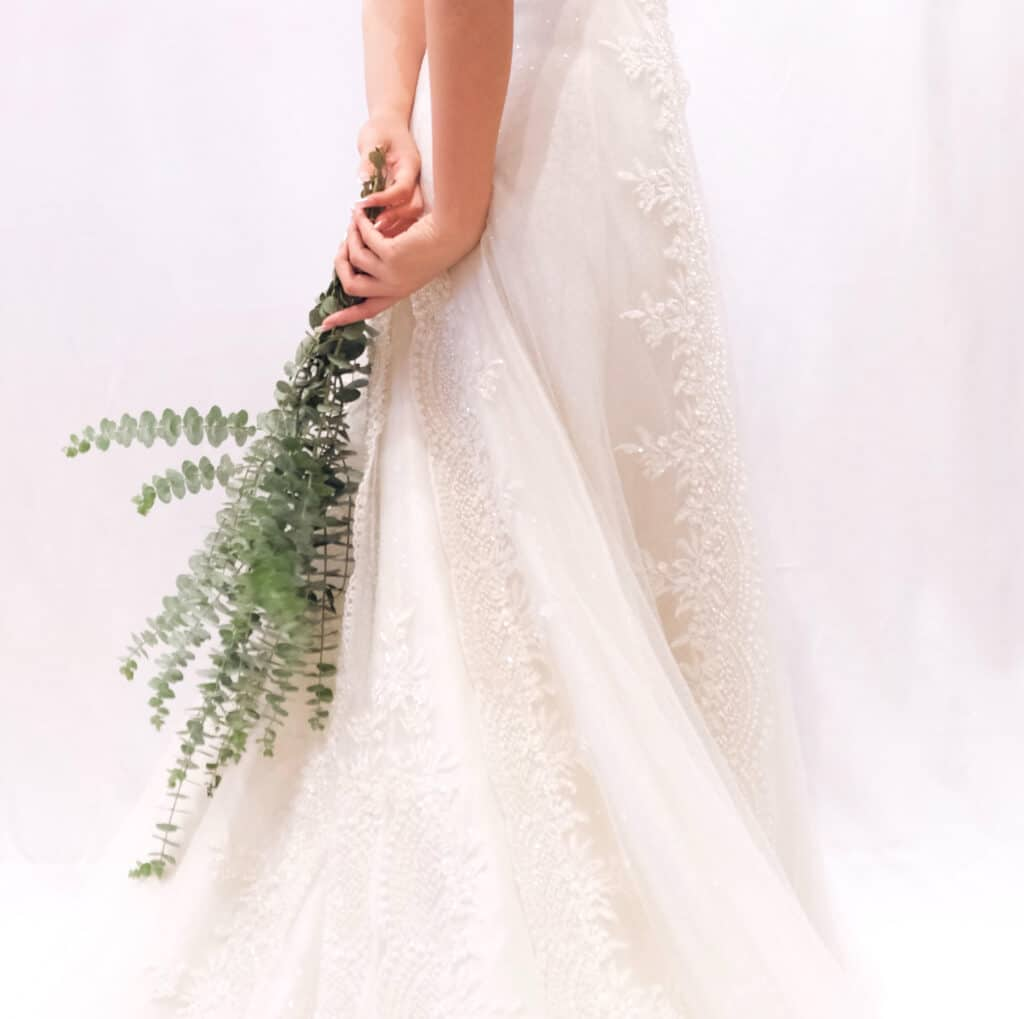 bride holding bouquet of long greenery behind her back