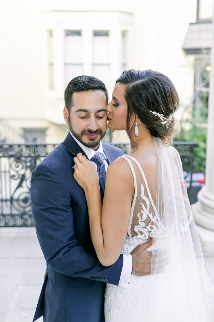 Bumby Photography - bride kissing groom on cheek on rooftop
