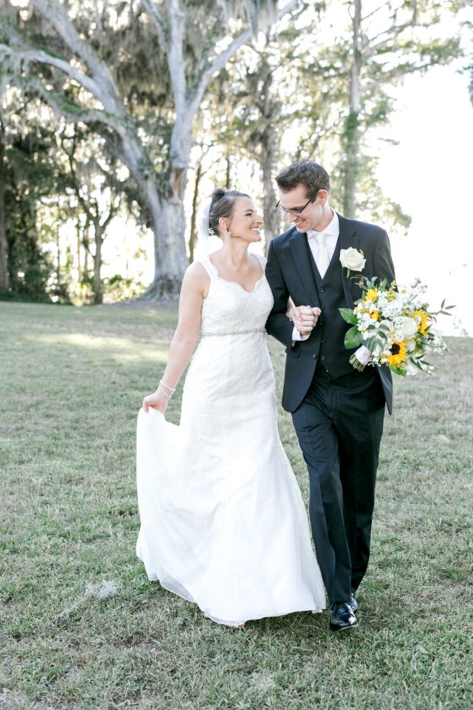 Bumby Photography - bride and groom holding hands and walking through grass
