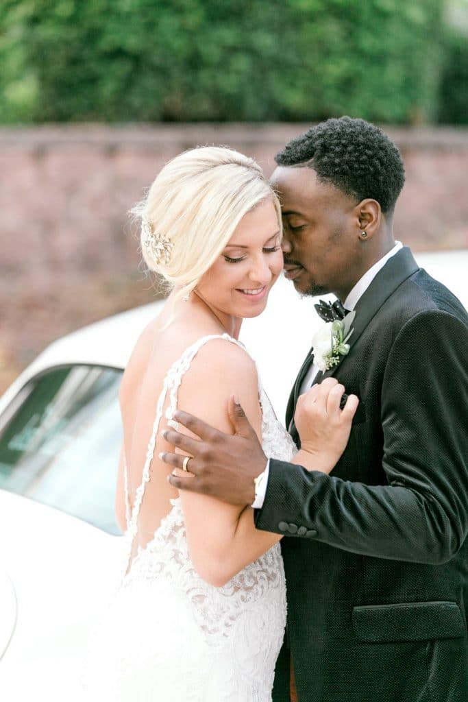 Bumby Photography - attractive couple embracing next to white classic car