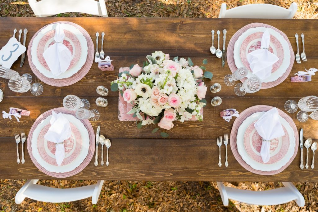 C-Squared-Events-LLC-Topview of light pink and white table setting with pink and white floral centerpiece on wooden table
