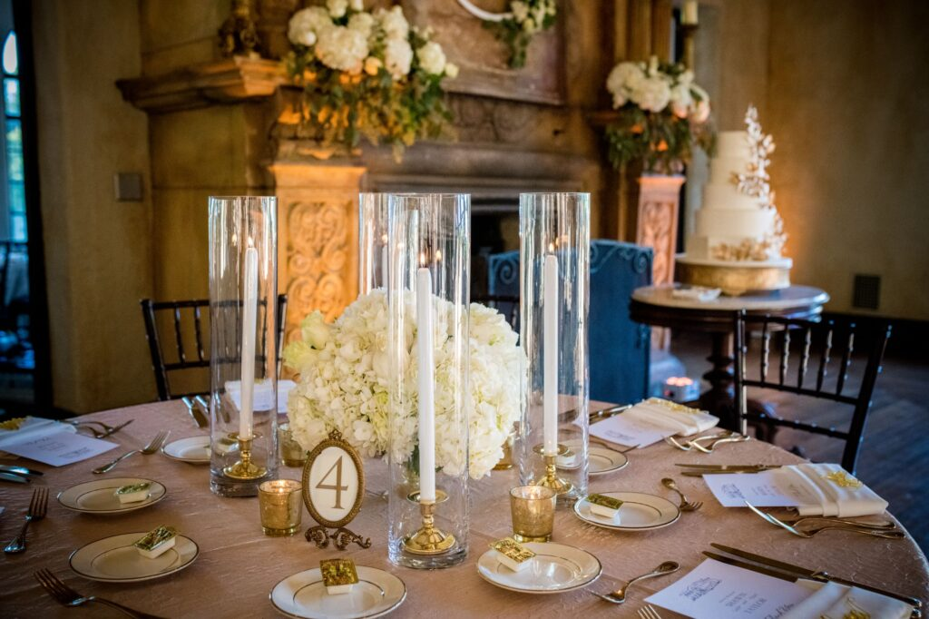 flower centerpieces for dinner table at wedding reception, with matching flowers on fireplace mantle in background