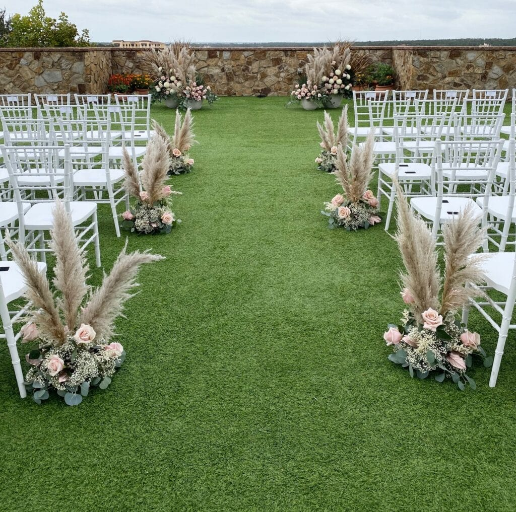flower decorations on the end of each row of seats for wedding ceremony and matching flower decorations behind where bride and groom will be standing