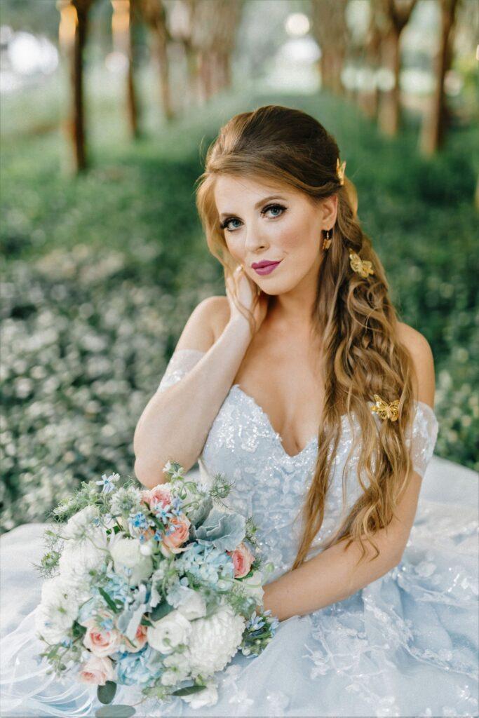 bride sitting in garden in her wedding dress holding flower bouquet