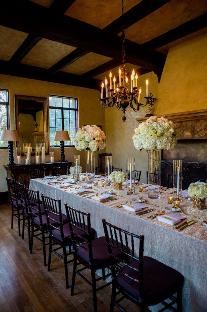 matching tall and short flower centerpieces arranged on one long table for guests of wedding reception