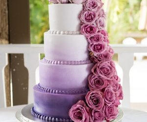 Cake and Bake- White to purple ombre cake with varying pink flowers cascading down each tier