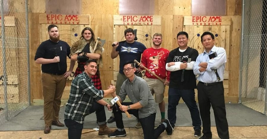 Epic-Axe-Throwing-group of people posing with axes in front of target boards in range
