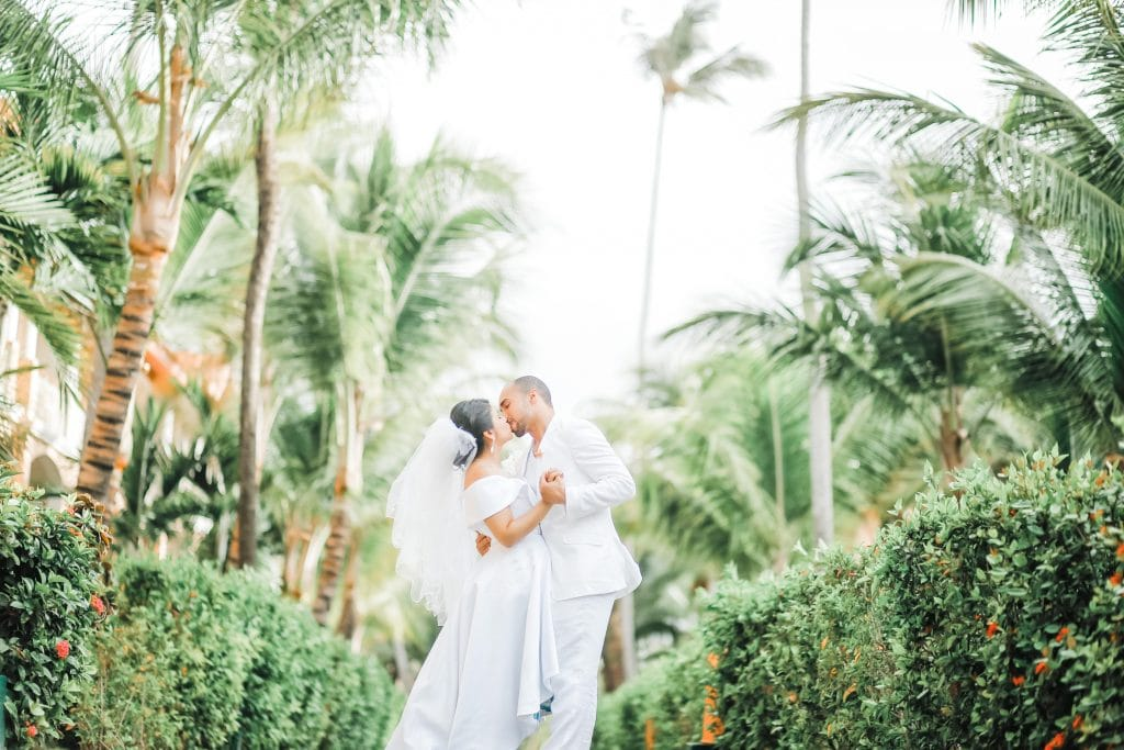bride and groom wearing white dress and suit and kissing surrounded by palm trees