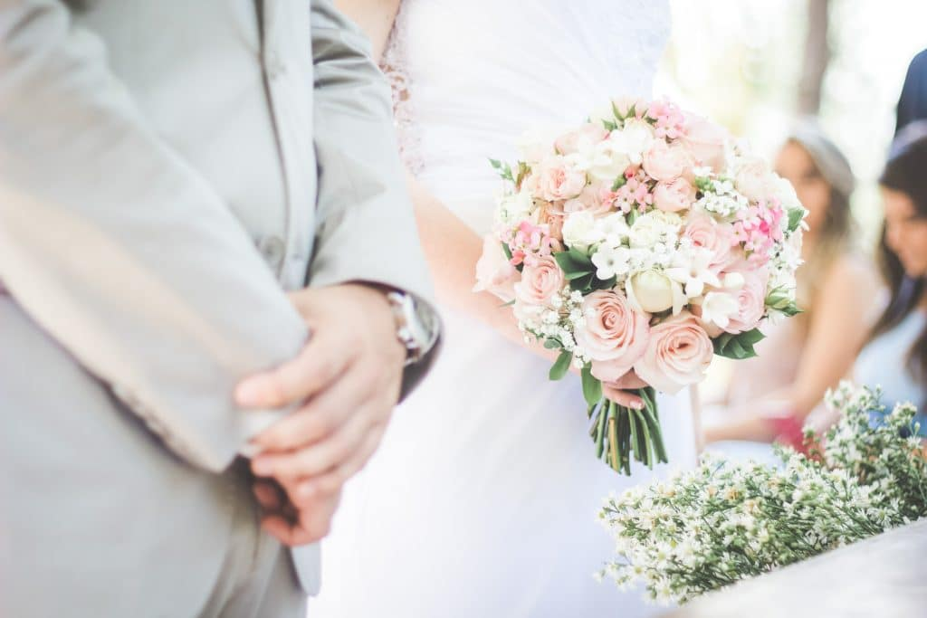 bride holding pink and white flowers next to groom in gray suit