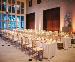 John-Michael-Catering - Large group dinner setting with white table covering and gold accents
