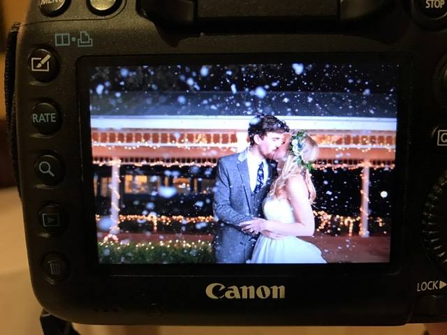 P.S. I Love You Productions - photo of kissing bride and groom on camera display screen