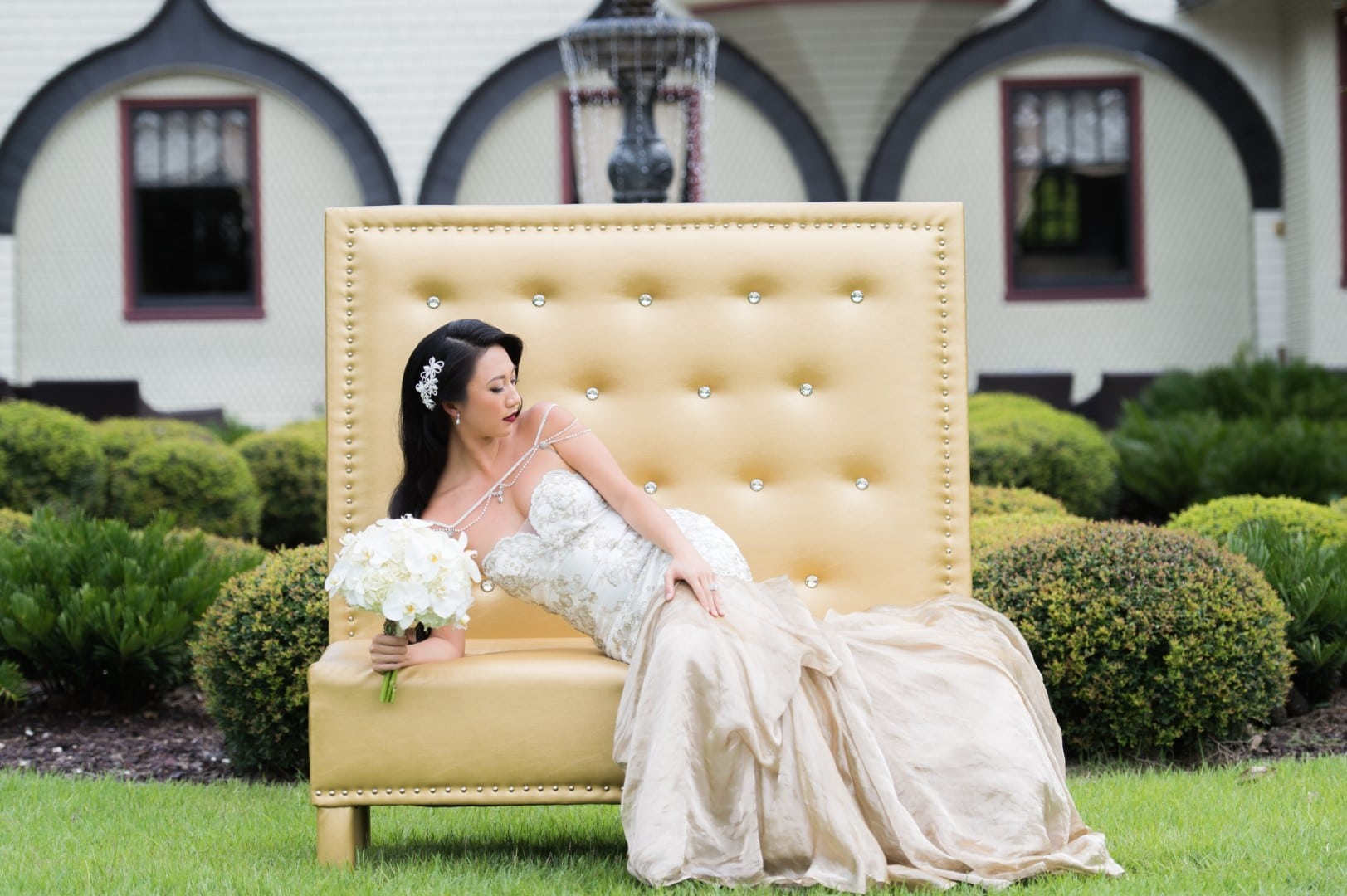 Pearl-White-Events-Bride leaning on elbow sitting on top of a gold colored cushioned chair in dress