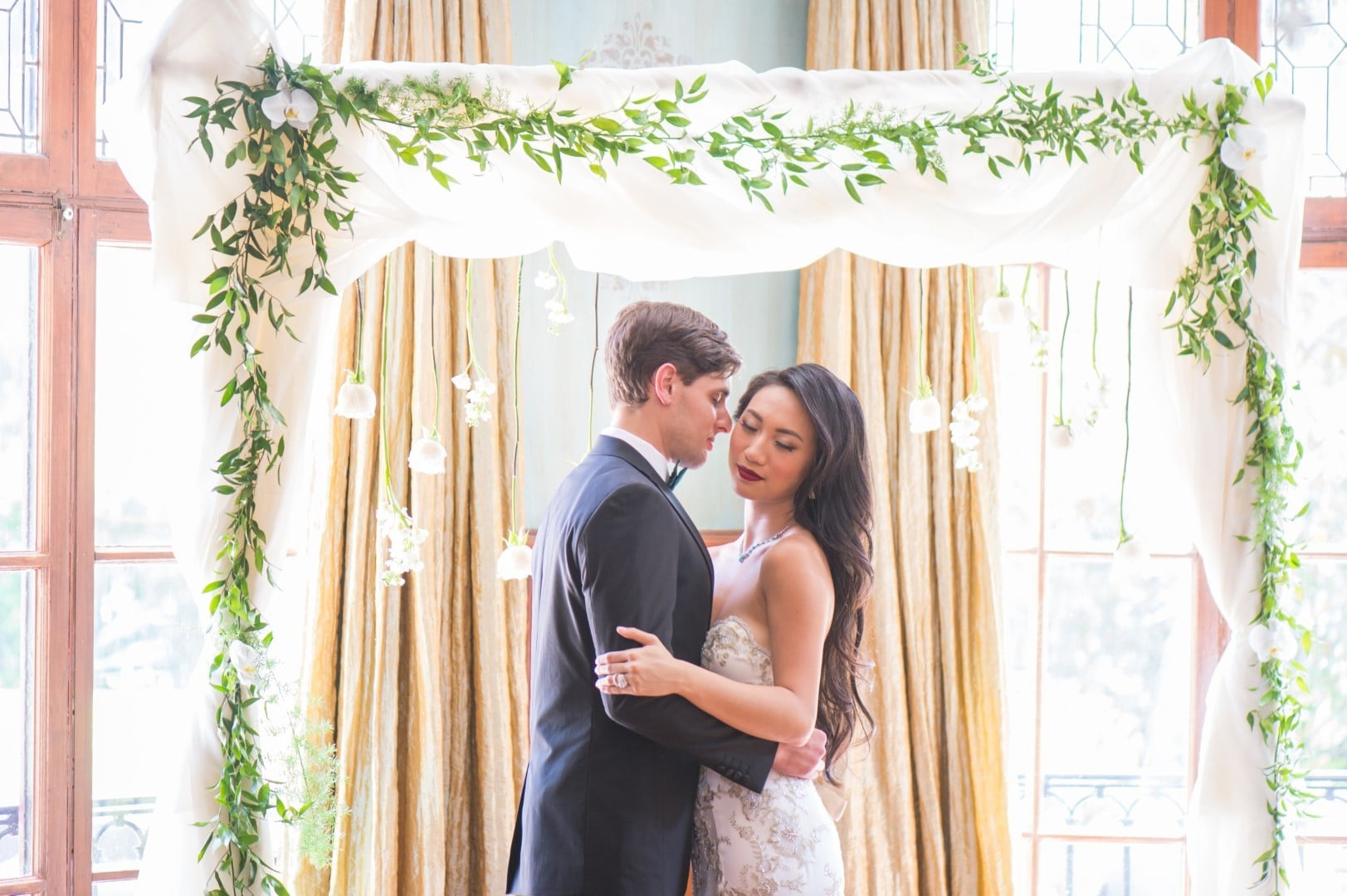 Pearl-White-Events-Bride and Groom standing under square greenery back drop with lights