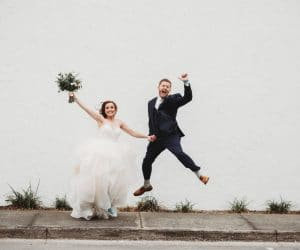 Rachel-Doyle-Photograhy-Bride and Groom jumping with joy in front of white wall