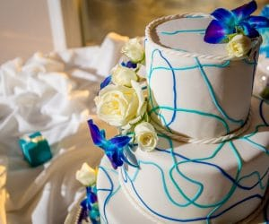 Sofelle-Cake-Artistry-Three tier whimsical lines pattern in shades of blue with tropical blue flowers and white roses