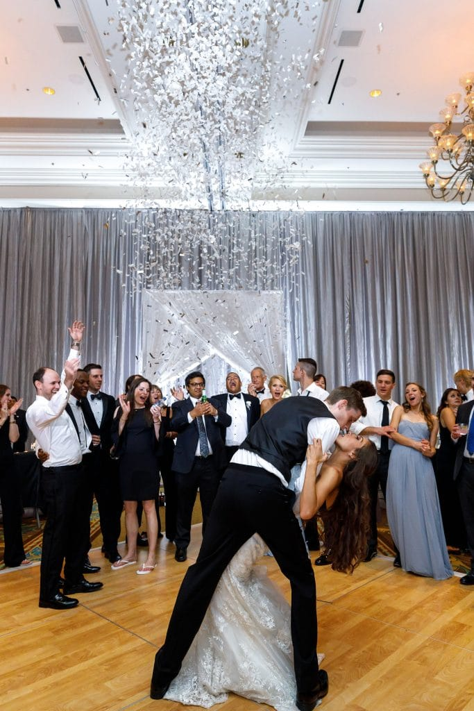 White Rose Entertainment - groom dipping bride on dance floor under a shower of silver confetti
