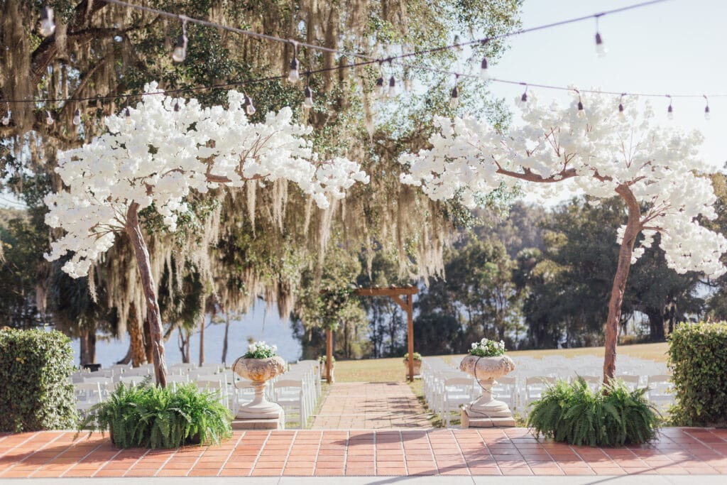outdoor wedding ceremony under large oak tree with hanging moss and white floral decor