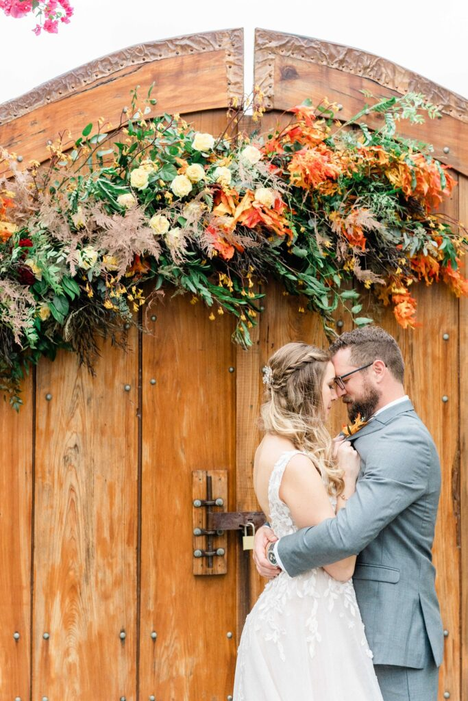 bride and groom hugging in front of wooden door with large floral garland