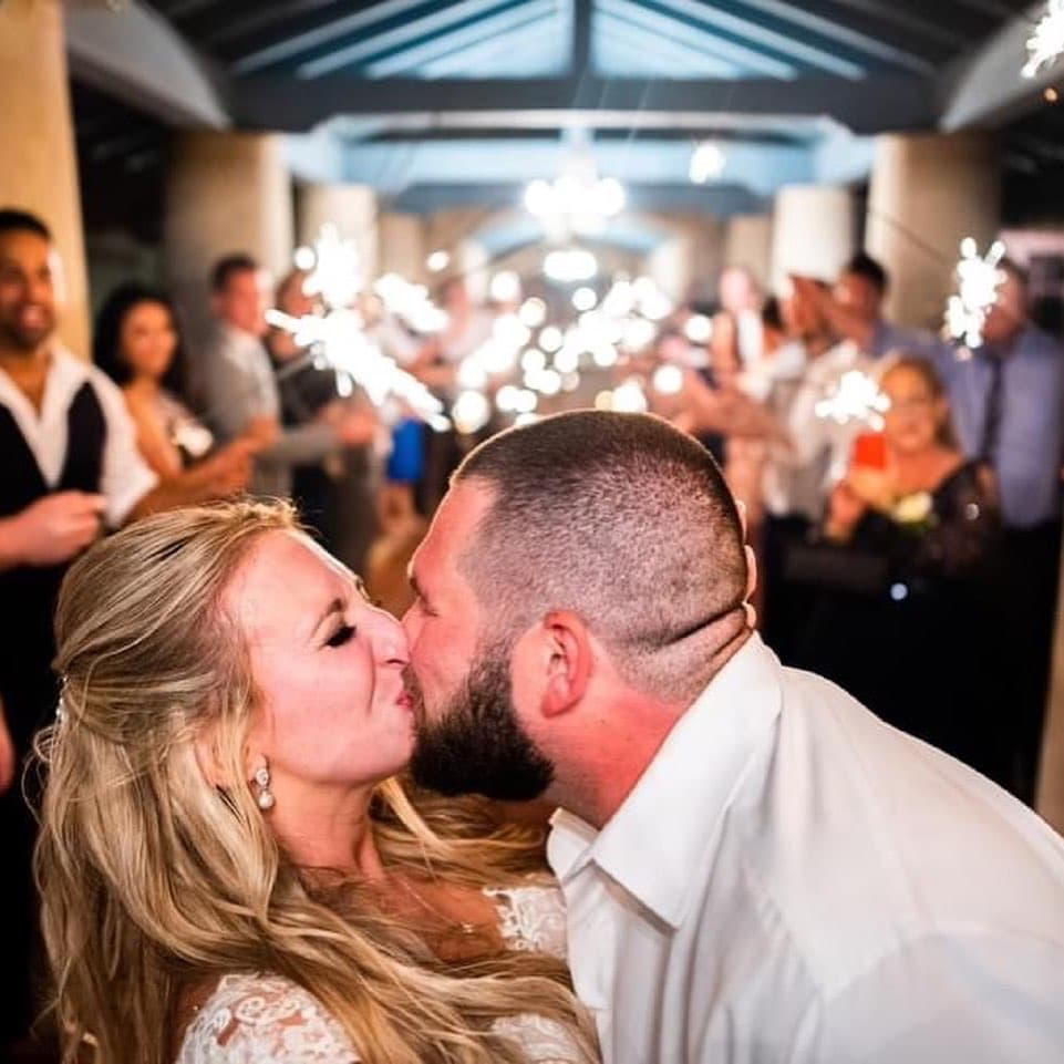 bride and groom kissing while guests hold sparklers behind them