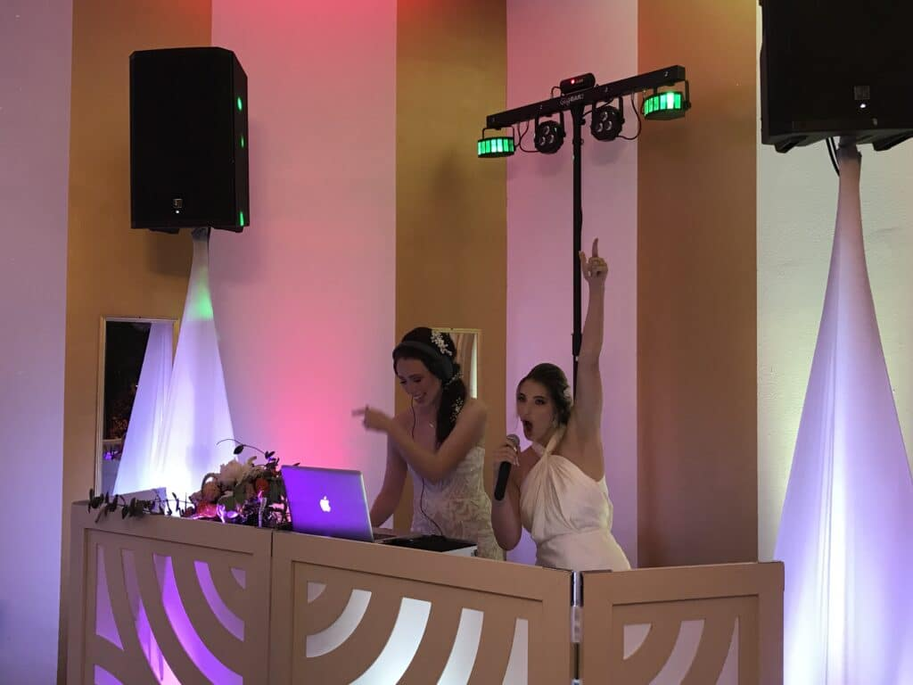 bride and a bridesmaid mixing music on the DJs setup