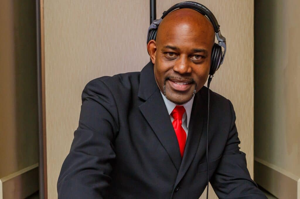 dj in a suit and wearing headphones