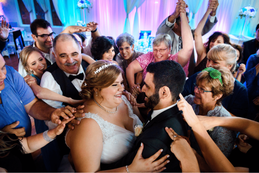 bride and groom dancing while their guests crowd around them