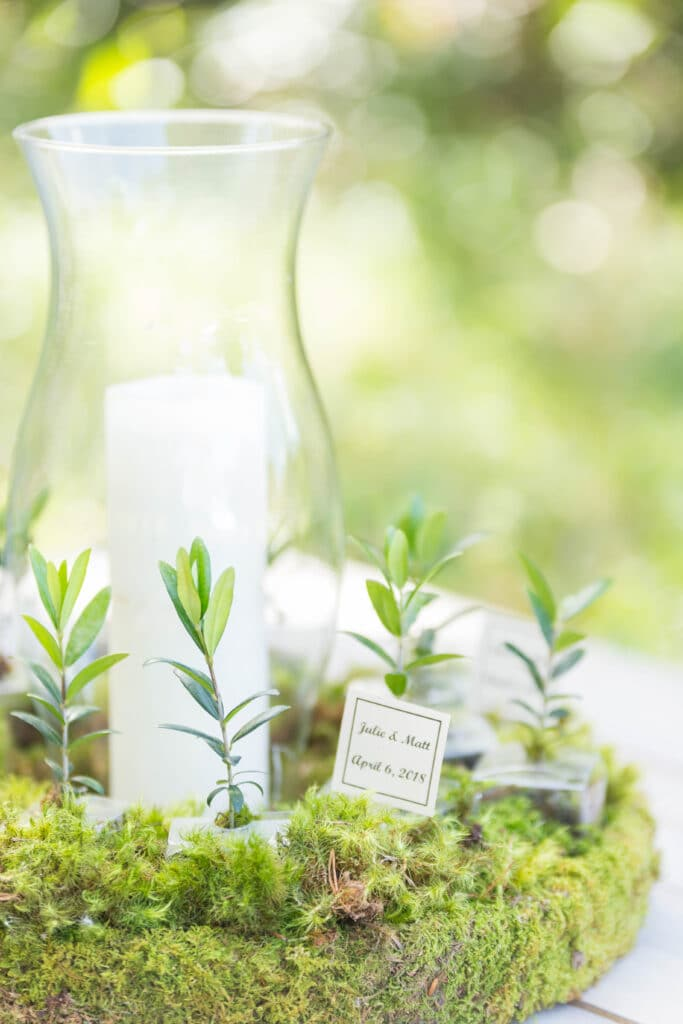 wedding decor with tall candle in vase surrounded by moss and greenery by the magnolia company florida