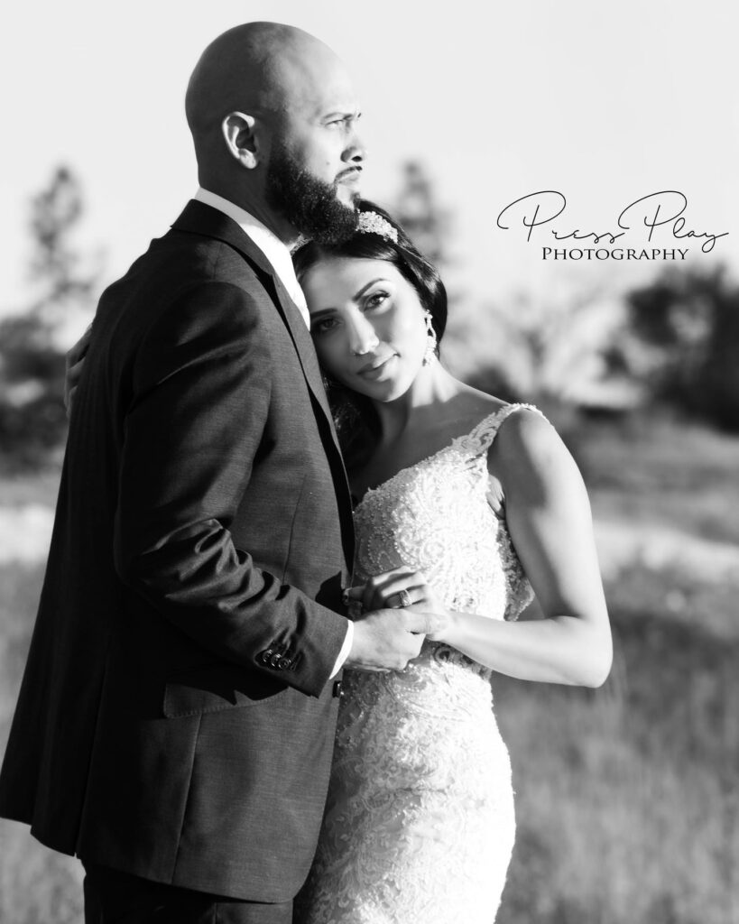 black and white image of bride and groom hugging and holding hands outdoors