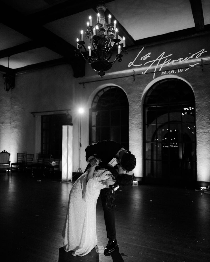 black and white image of groom along on dance floor under chandelier
