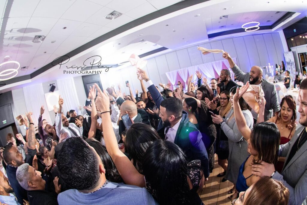 wedding guests on dance floor in white room with hands up