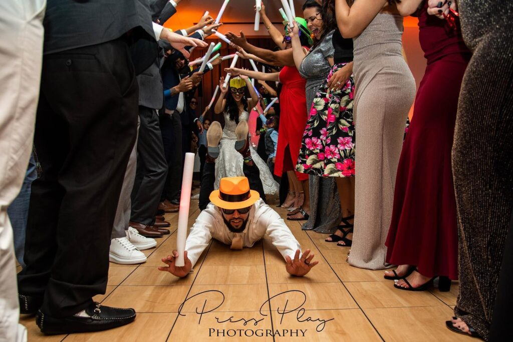 man sliding on floor toward camera with wedding guests on either side of him holding glow sticks