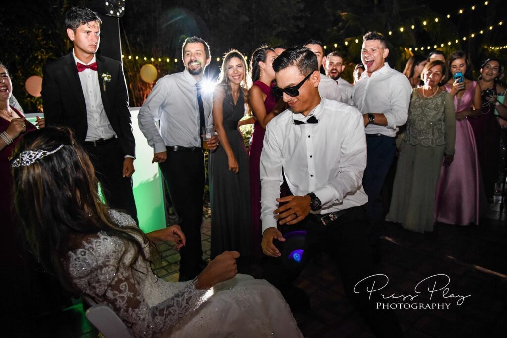 groom with sunglasses dancing in front of bride who is sitting in chair while guests cheer them on