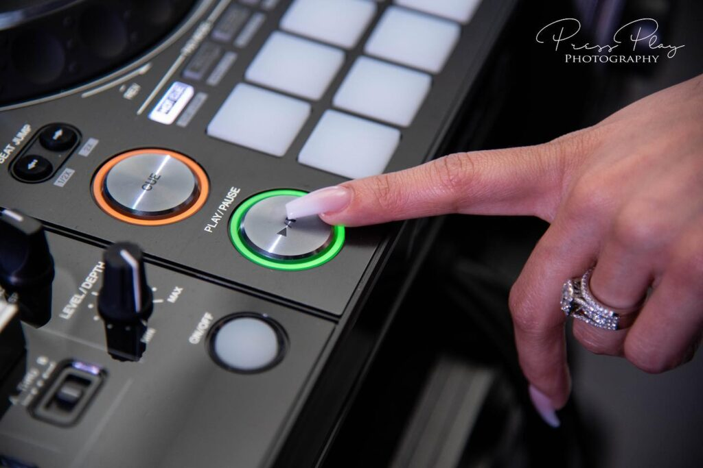 finger pressing round button with green light on dj equipment