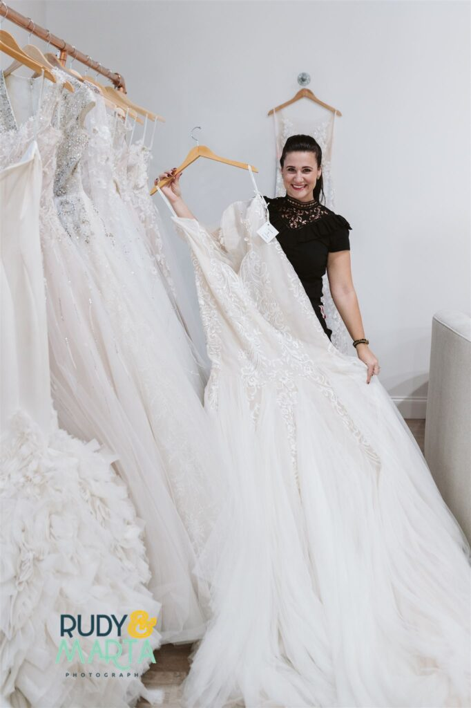 woman in black dress holding long wedding dress out from rack - bridal finery orlando wedding gowns