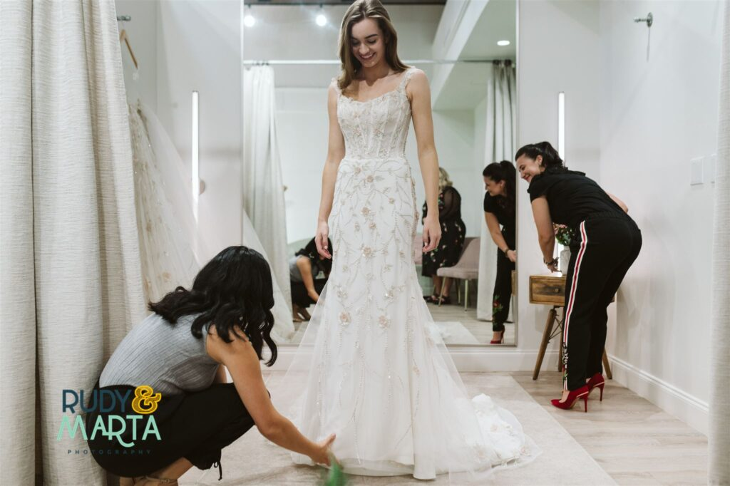 bride trying on long lace dress with cap sleeves at bridal shop - bridal finery orlando wedding gowns